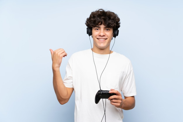 Junger mann, der mit einem videospielcontroller über lokalisierter blauer wand zeigt auf die seite spielt, um ein produkt darzustellen