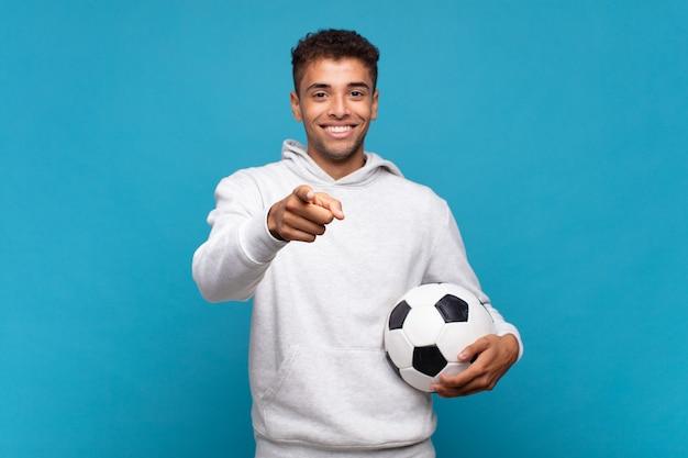 Junger mann, der mit einem zufriedenen, selbstbewussten, freundlichen lächeln auf kamera zeigt und sie wählt. fußballkonzept