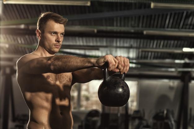 Junger mann, der mit einer kesselglocke im fitnessstudio arbeitet