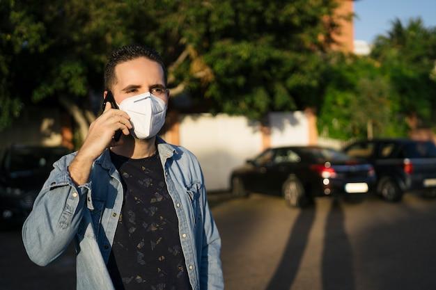 Junger mann, der mit einer medizinischen maske auf seinem gesicht anruft
