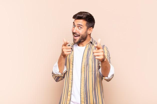 Junger mann, der mit einer positiven, erfolgreichen, glücklichen haltung lächelt, die auf die kamera zeigt und waffenzeichen mit händen macht