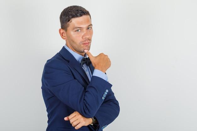 Junger mann, der mit finger am kinn im anzug lächelt