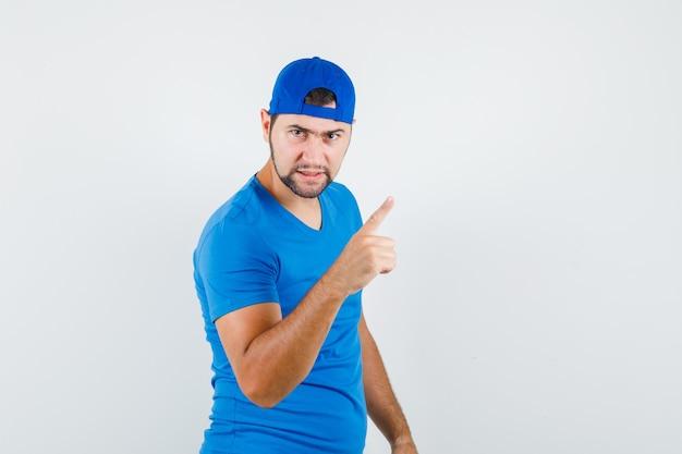 Junger mann, der mit finger im blauen t-shirt und in der mütze warnt und wütend schaut