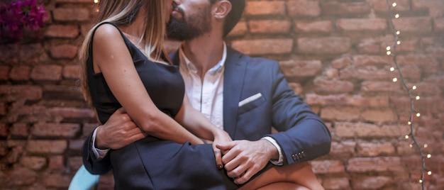 Junger mann, der mit frau auf stuhl küsst