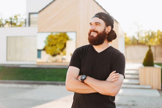 Junger mann, der mit gekreuzten händen vor seinem neuen haus steht, lächelt und wegschaut