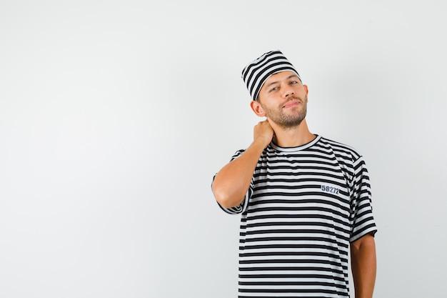 Junger mann, der mit hand am hals im gestreiften t-shirt, im hut und im eleganten blick aufwirft.