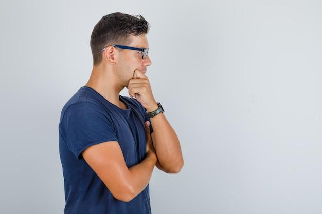 Junger mann, der mit hand auf kinn im blauen t-shirt, brille steht und nachdenklich schaut.