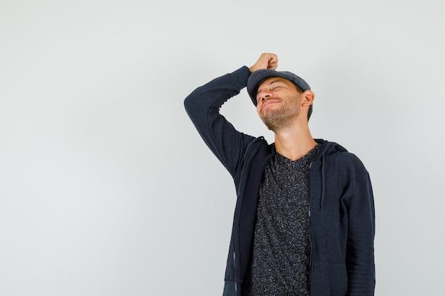 Junger mann, der mit hand auf kopf in t-shirt, jacke, mütze und friedlich aussehend aufwirft.