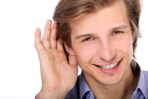 Junger mann, der mit hand auf ohr hört