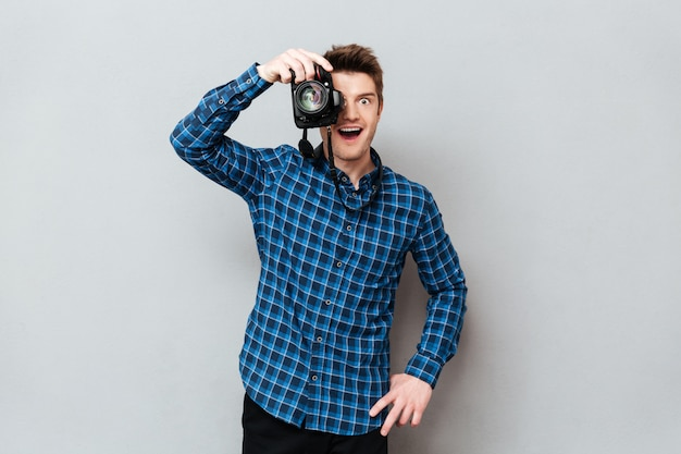 Junger mann, der mit kamera arbeitet