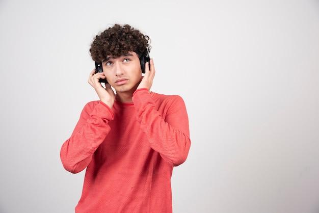 Junger mann, der mit kopfhörern musik hört.