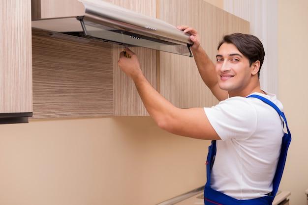 Junger mann, der mit küchenausrüstung arbeitet