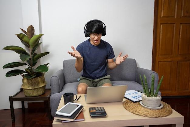 Junger mann, der mit kunden auf dem sofa anruft oder auf videoanruf mit kollegen spricht