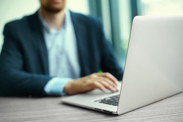 Junger mann, der mit laptop, die hände des mannes auf notebook, geschäftsperson am arbeitsplatz arbeitet