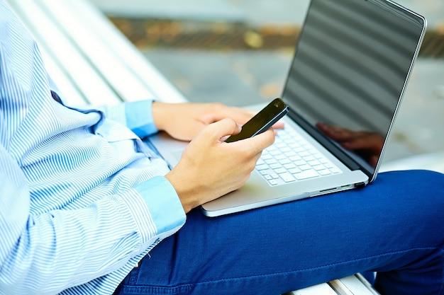 Junger mann, der mit laptop, mannhänden auf notizbuchcomputer, geschäftsmann in der freizeitkleidung in der straße arbeitet
