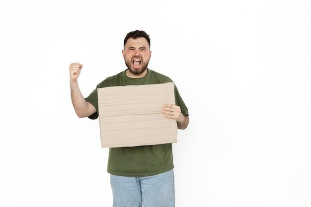Junger mann, der mit leerem brettzeichen auf weißem studiohintergrund protestiert