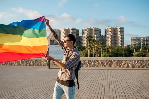 Junger mann, der mit lgbt-flagge steht