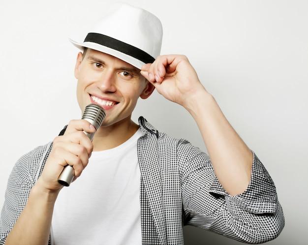 Junger mann, der mit mikrofon singt