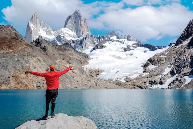 Junger mann, der mit offenen armen steht und glücklich auf den monte fitz roy und die laguna de los tres starrt