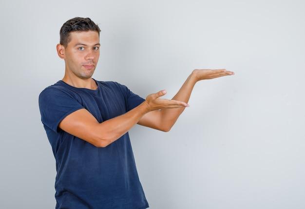 Junger mann, der mit palmen im dunkelblauen t-shirt, vorderansicht präsentiert.