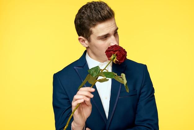 Junger mann, der mit rose aufwirft