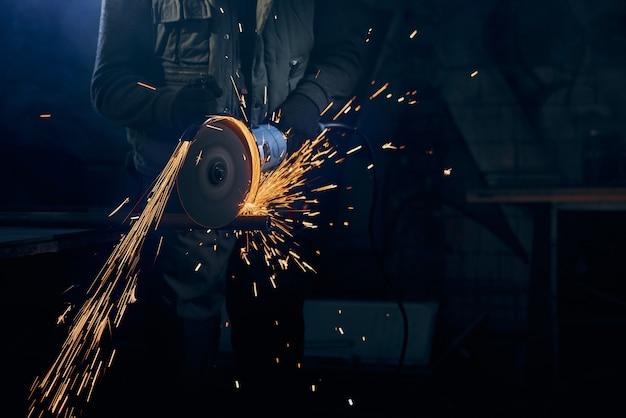Junger mann, der mit rotierender scheibe für metall mit funken schneidet