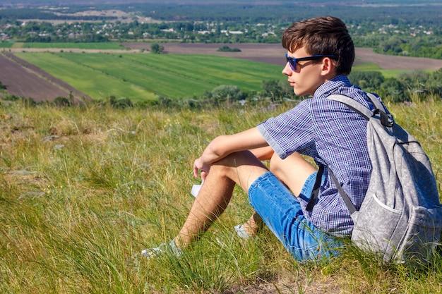 Junger mann, der mit rucksack sitzt und schöne aussicht, tourismuskonzept betrachtet