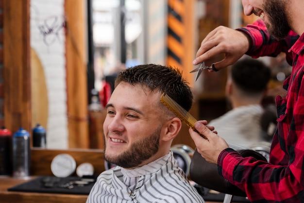 Junger mann, der mit scheren und kamm trimmt