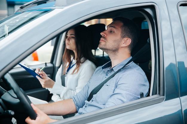 Junger mann, der mit seinem ausbilder ein auto fährt