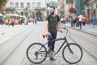 Junger Mann, der mit seinem Fahrrad in der Stadt steht