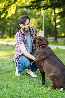 Junger Mann, der mit seinem Hund auf grünem Gras spielt