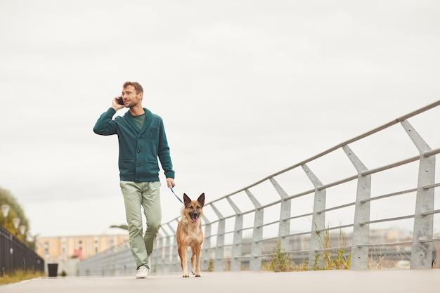 Junger mann, der mit seinem hund entlang der straße geht und auf handy spricht
