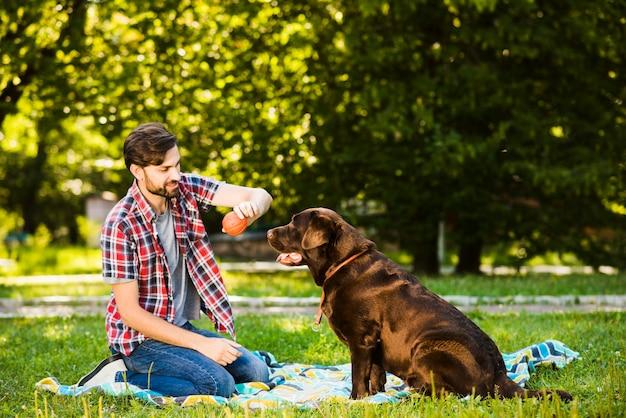 Junger mann, der mit seinem hund im garten spielt