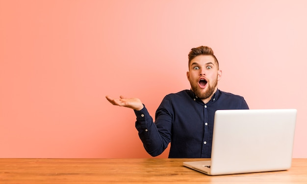 Junger mann, der mit seinem laptop arbeitet, beeindruckte das halten des kopierraums auf der handfläche.