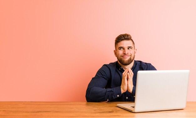 Junger mann, der mit seinem laptop arbeitet, der plan plant, eine idee aufstellt.