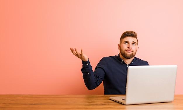 Junger mann, der mit seinem laptop arbeitet und zwischen zwei optionen zweifelt.