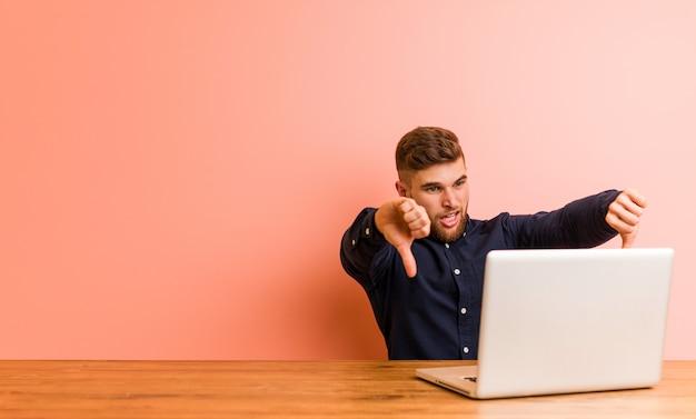 Junger mann, der mit seinem laptop unten zeigt daumen arbeitet und abneigung ausdrückt.