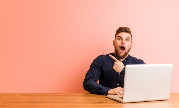 Junger mann, der mit seinem laptop zeigt auf die seite arbeitet