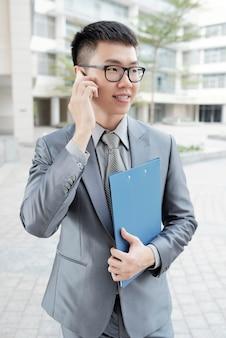 Junger mann, der mit seinem smartphone nennt