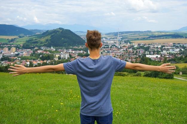 Junger mann, der mit seinen händen offen in ruzomberok, slowakei steht