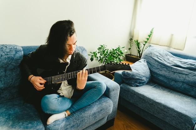 Junger mann, der mit seiner e-gitarre auf dem sofa seines hauslernens übt.