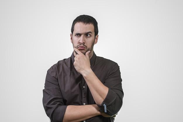 Junger mann, der mit seiner hand auf seinem gesicht und hemd denkt