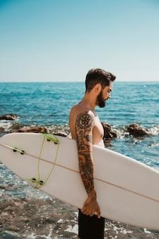 Junger mann, der mit surfbrett auf strand steht