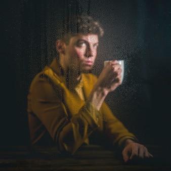 Junger mann, der mit tasse kaffee aufwirft