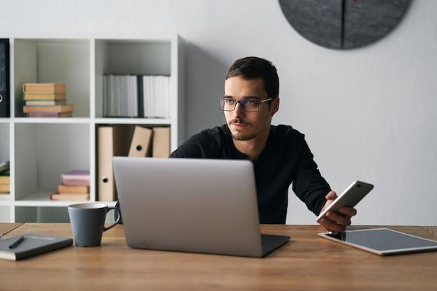 Junger mann, der mit telefon und computer arbeitet, telefonanrufe empfängt, mit partnern spricht