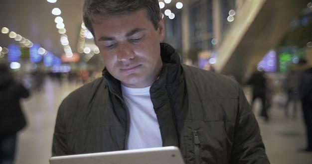 Junger mann, der mit touchpad am flughafen arbeitet