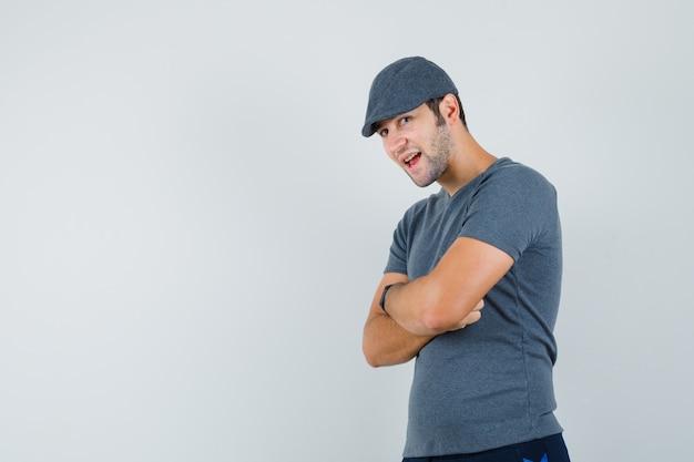 Junger mann, der mit verschränkten armen im grauen t-shirt, mütze und selbstbewusst aussehend, vorderansicht steht.