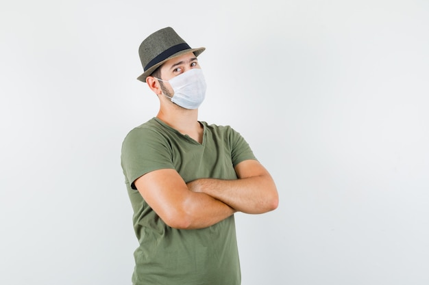 Junger mann, der mit verschränkten armen im grünen t-shirt und im hut, in der maske steht und zuversichtlich schaut
