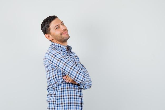Junger mann, der mit verschränkten armen im karierten hemd aufwirft und fröhlich schaut
