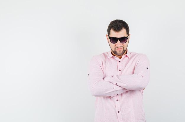 Junger mann, der mit verschränkten armen im rosa hemd steht und zuversichtlich schaut